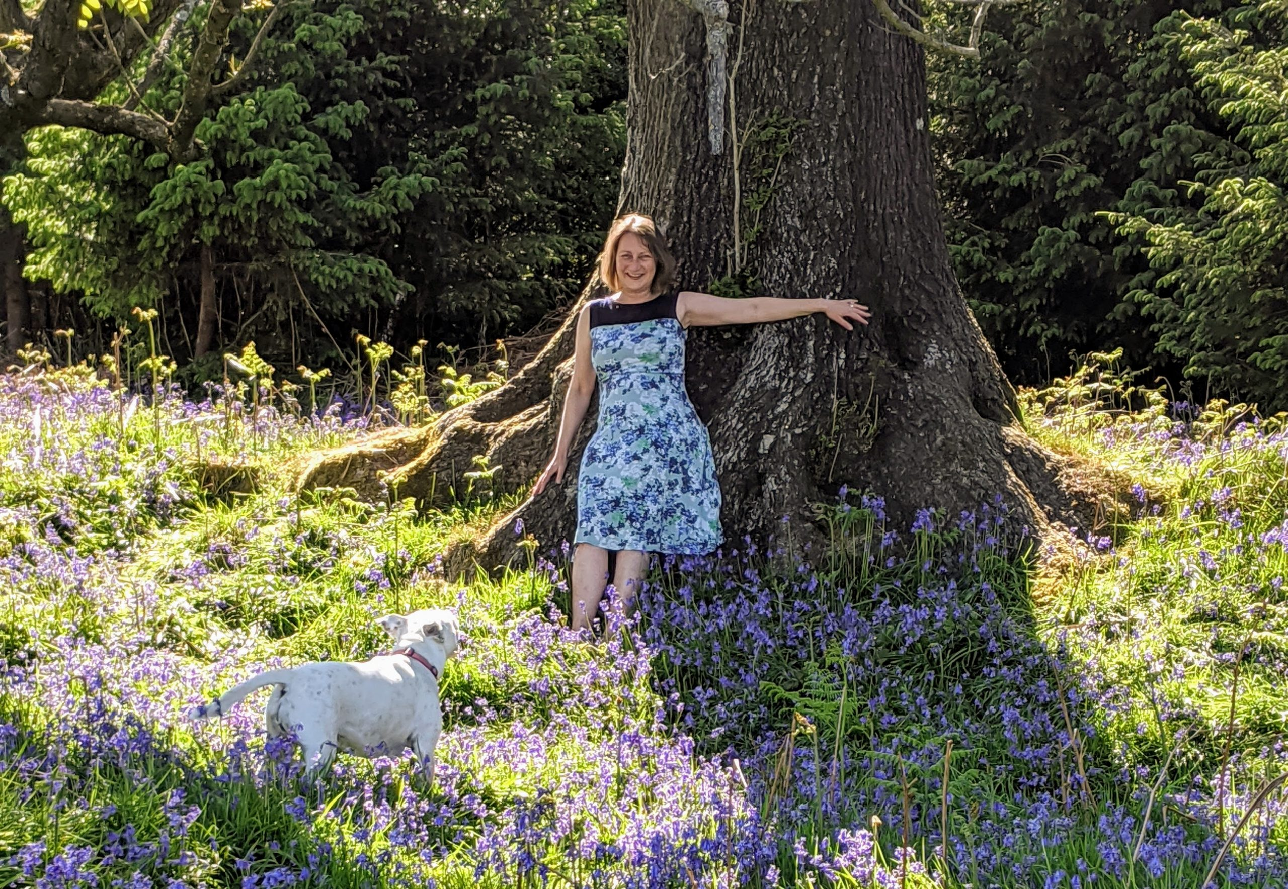 Jenny Bracelin leaning on a tree surrounding by bluebells